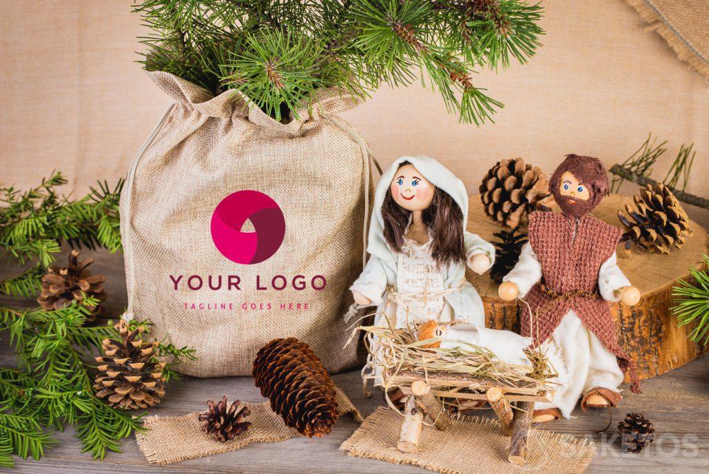 Crèche de Noël et vase avec une branche de conifère placés dans un sac en jute
