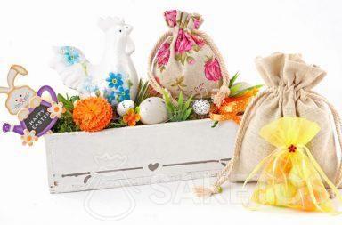 Une composition de Pâques crée avec des sachets tissu et un pot-à-fleurs rectangulaire avec des œufs colorés
