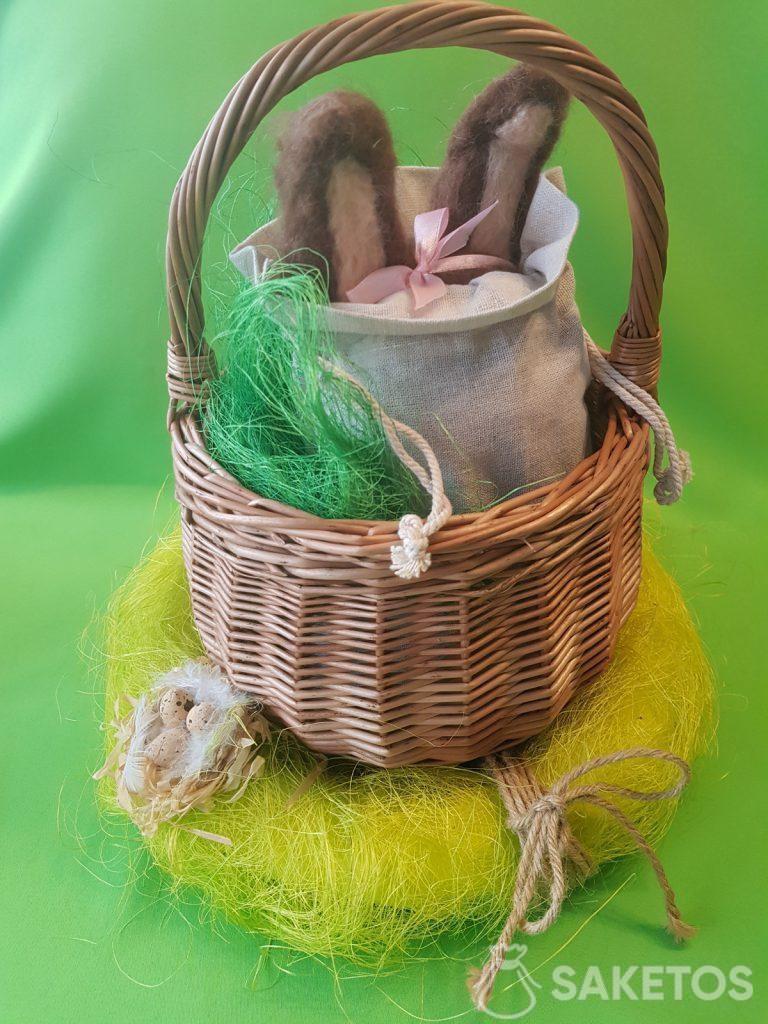 Petit panier avec un sac en lin dont dépassent les oreilles d'un lapin feutré en laine peignée.
