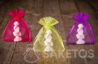 Figurines d'anges emballées dans les pochettes en organdi colorées comme cadeaux remerciement invités mariage