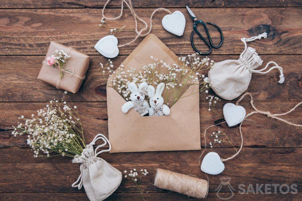 Sac en lin avec plâtre, lapins en peluche dans une enveloppe et un cadeau emballé dans du papier gris