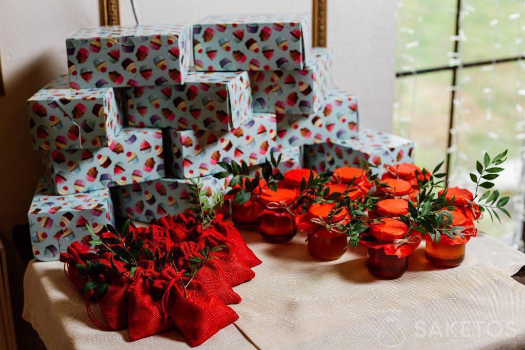 Coffrets cadeaux emballés dans du papier de couleur, sacs en jute rouge et bocaux avec conserves