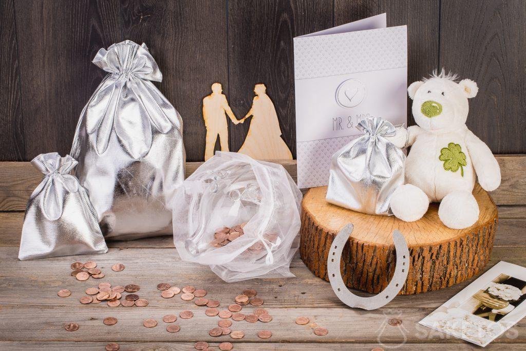 Lorsque le cadeau de mariage est censé être de l'argent, vous pouvez l'envelopper dans une tirelire en verre placée dans un sac en organza.
