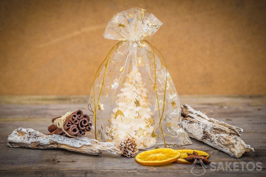 Une bougie en forme de sapin de Noël dans un sachet en organdi.