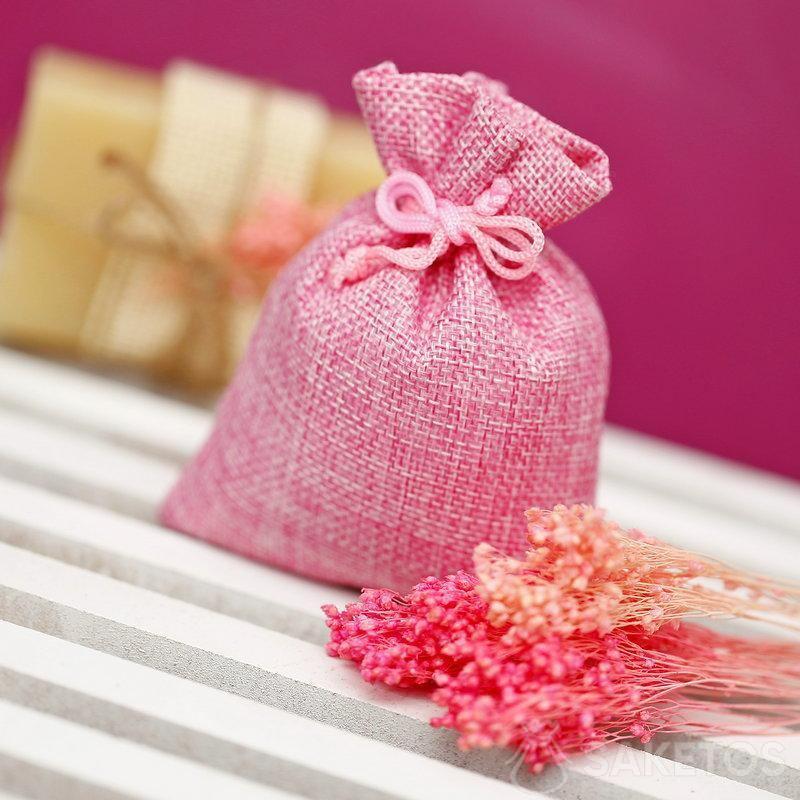 Une pochette en jute rose pour empaqueter une savonnette naturelle.