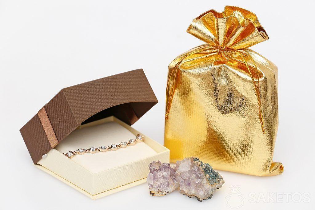 Sac en satin d'argent comme emballage élégant pour une boîte à bijoux en carton avec boucles d'oreilles.