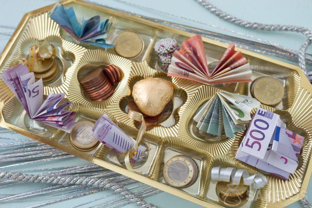 Les billets de banque et de la monnaie rangés dans une boîte de pralinés
