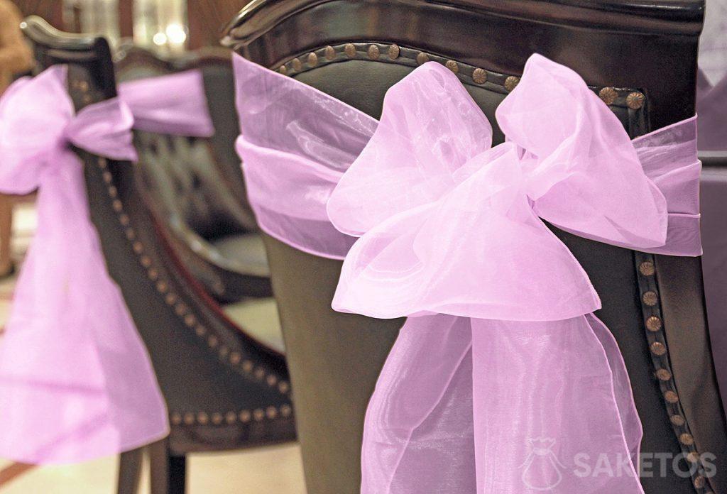 Un nœud de ruban décoratif en organdi réalisé avec le dossier de la chaise.