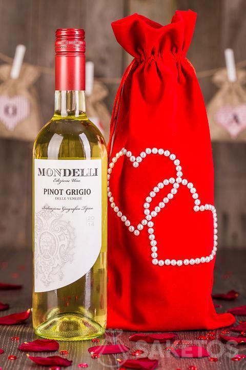 Une bouteille de vin en cadeau emballée dans un sachet décoratif en velours rouge