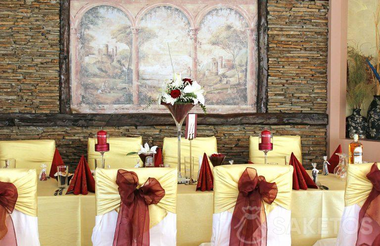 1.Le dressage de table de couleur bordeaux - vase, serviettes de table, chandeliers et nœuds de ruban sur les chaises