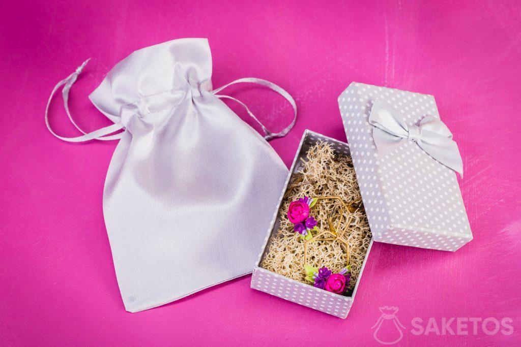 Les boucles d'oreille dans une boîte cadeau pour bijoux enveloppée dans une pochette