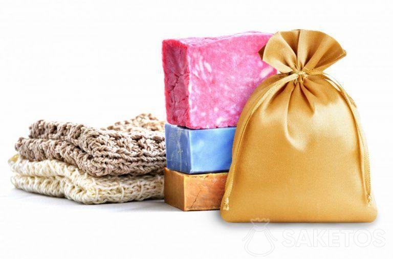 Un sac en satin doré sur un fond de savons colorés.