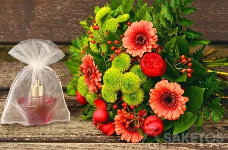 L'ensemble cadeau pour femme - un bouquet de fleurs et un flacon de parfum dans un sachet en organza