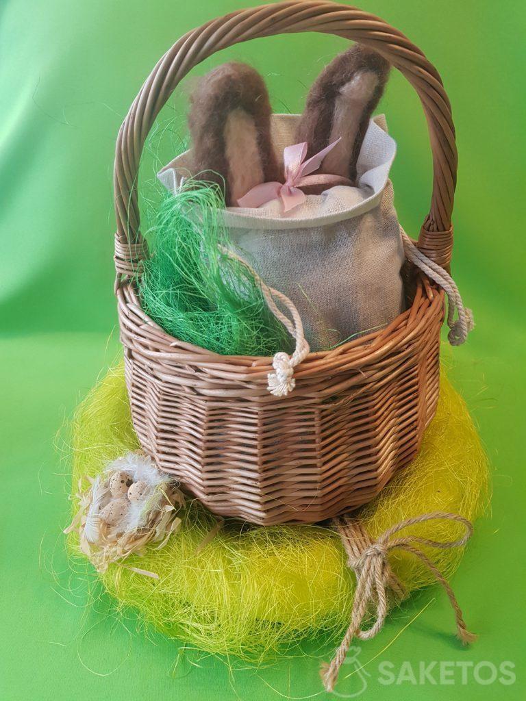 Un panier avec un sac en lin, d'où sortent les oreilles de laine de lapin en feutre.