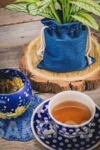 4.La tasse céramique avec du thé et le sac en jean pour un pot de fleurs